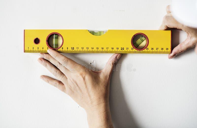 Reparador que trabalha com ruller de medição na parede fotografia de stock