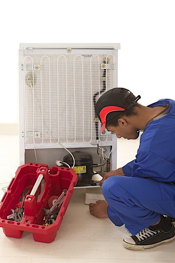 Reparador que trabalha em um refrigerador quebrado imagens de stock royalty free