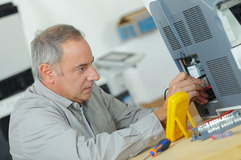 Reparador que trabalha no computador no centro de serviço imagem de stock