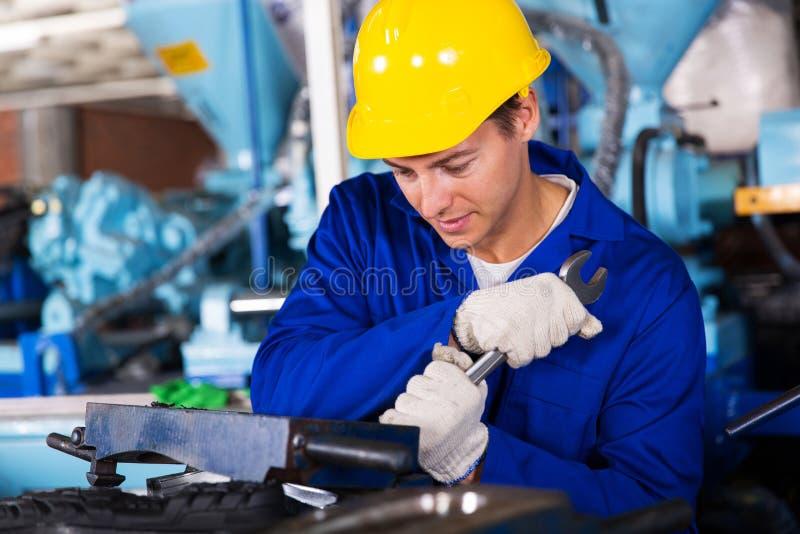 Reparador que usa a la llave inglesa foto de archivo