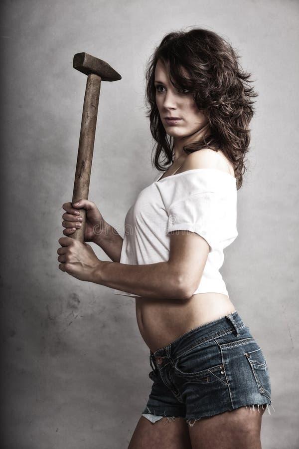 Reparador 'sexy' da menina que guarda a ferramenta do martelo imagem de stock royalty free