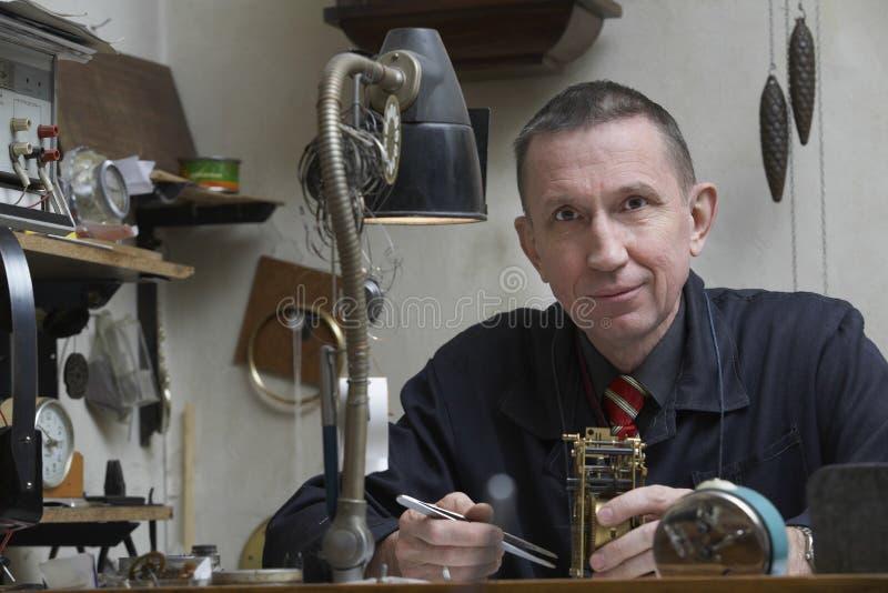 Reparador Working On Clock en taller foto de archivo