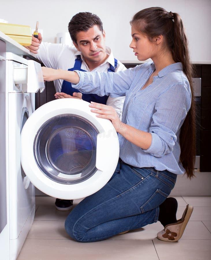 Reparador y mujer cerca de la lavadora foto de archivo