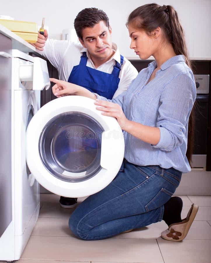 Reparador y mujer cerca de la lavadora imagenes de archivo
