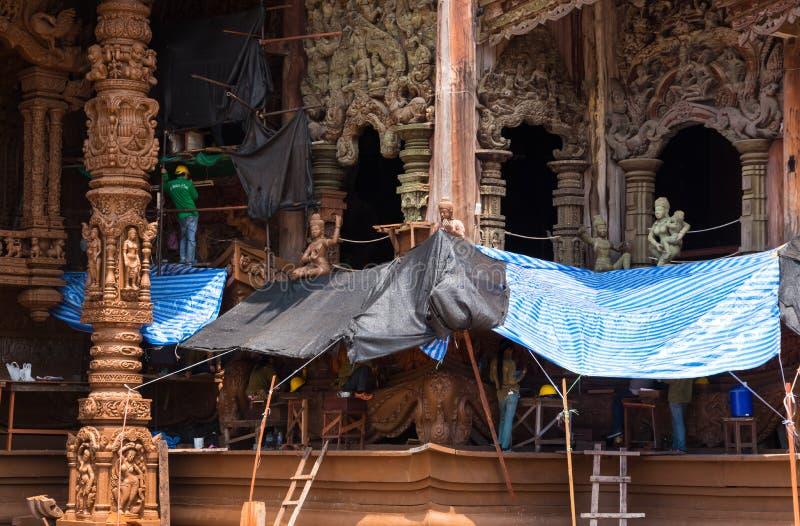 Reparadores y mujeres en el sitio de la restauración en el exterior del lado del santuario de la verdad, Tailandia foto de archivo libre de regalías