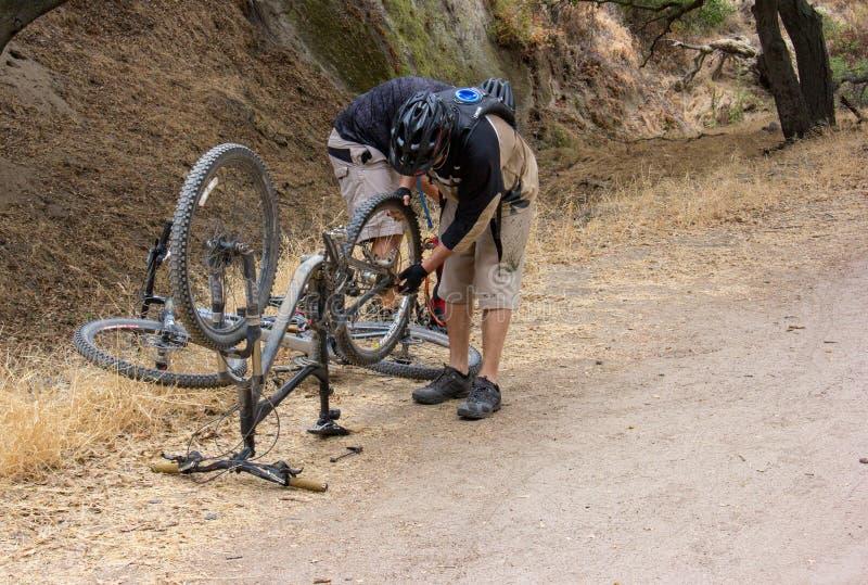 Reparando um Mountain bike no parque da região selvagem do rancho das pescadas fotografia de stock