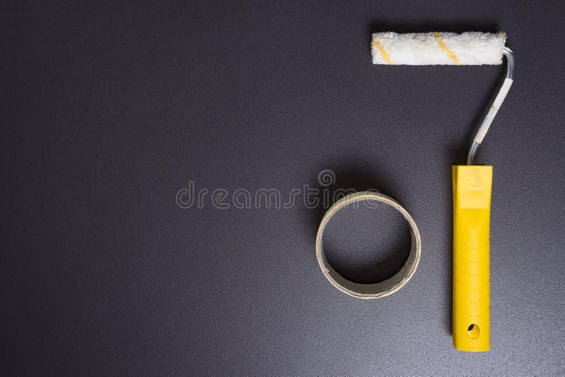 Reparatie binnenshuis concept Rol voor het schilderen en verfband op zwarte achtergrond en vrije ruimte stock fotografie
