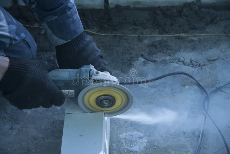 Reparatie en bouw van gebouwen De schijf van de cirkel malende machine roteert besnoeiingen witte baksteen stock afbeeldingen