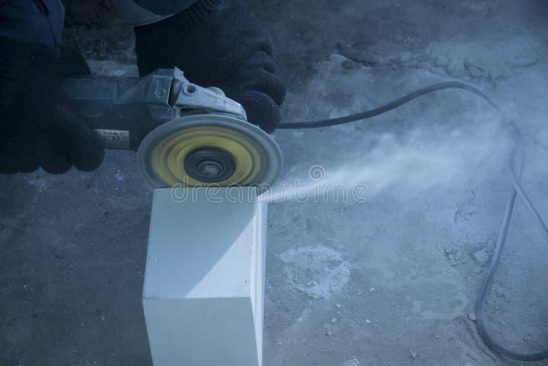 Reparatie en bouw van gebouwen De schijf van de cirkel malende machine roteert besnoeiingen witte baksteen stock foto
