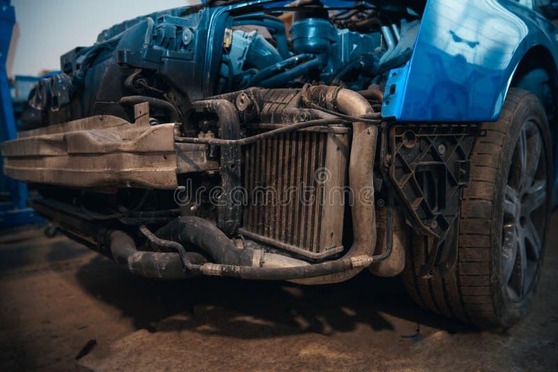 Reparatie en controleauto in reparatiewerkplaats Een ervaren technicus herstelt het defecte deel van de auto Ik verander banden stock fotografie
