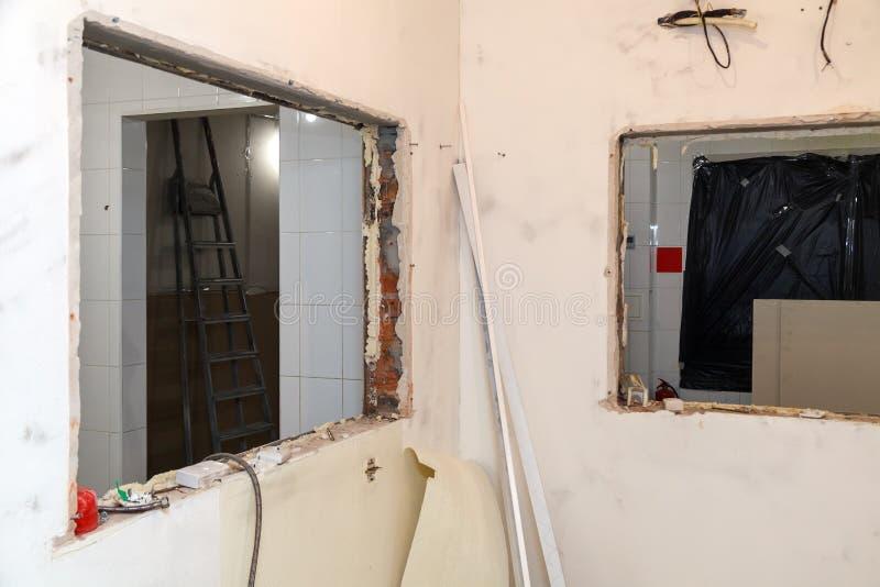 Reparatie en vervangingsvensters in de bureaubouw, vernietigde vensterverdelingen van bakstenen, tegels Het team van de concepten stock foto