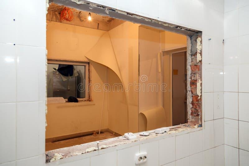 Reparatie en vervangingsvensters in de bureaubouw, vernietigde vensterverdelingen van bakstenen, tegels Het team van de concepten stock afbeelding