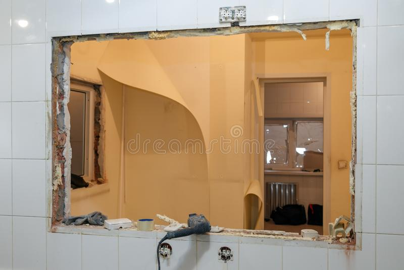 Reparatie en vervangingsvensters in de bureaubouw, vernietigde vensterverdelingen van bakstenen, tegels Het team van de concepten stock afbeeldingen