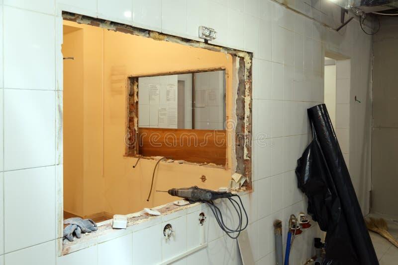Reparatie en vervangingsvensters in de bureaubouw, vernietigde vensterverdelingen van bakstenen, tegels Het team van de concepten stock fotografie