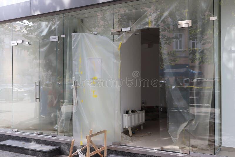 Reparatie van een moderne ruimte met glasmuren en ingangsdeuren Bouw en ontwerp van een handelsplatform Het schilderen de werken  royalty-vrije stock afbeeldingen
