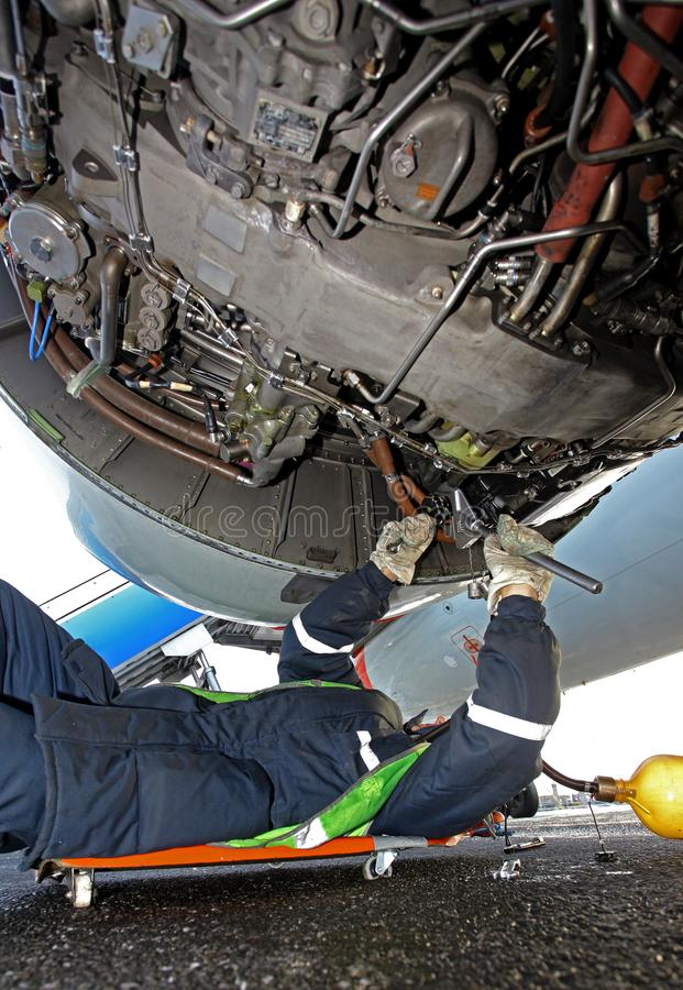 Reparatie van een vliegtuigenmotor op het startgebied stock afbeelding