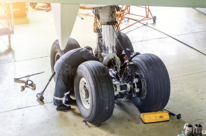 Reparatie van het chassis landingsgestel van de vliegtuigen, twee technici van werktuigkundigen aan het werk in de hangaar stock foto's