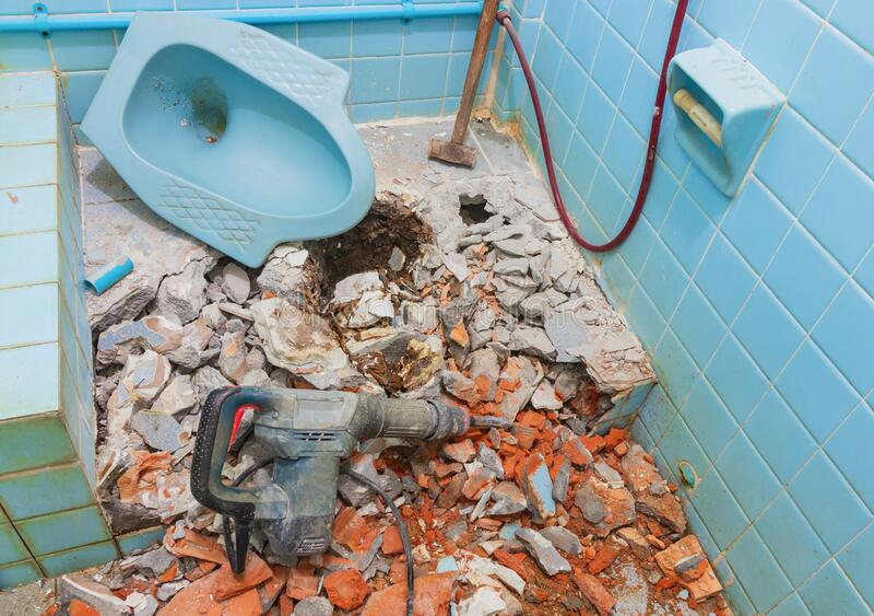 Reparatie van oude wc-binnenwc en pneumatische hamer met Grote stalen hamer royalty-vrije stock afbeeldingen