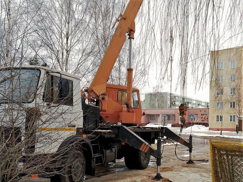 Reparatiebouwwerkzaamheden, het boren die van het goed scharnierende materiaal op de tractor, tegen de achtergrond van huizen wer royalty-vrije stock fotografie