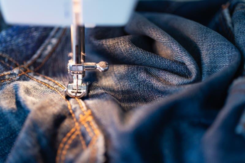 Reparatiejeans op de naaimachine Mening van de stof, de naald en de draad Verlichting van de ingebouwde gloeilamp stock foto