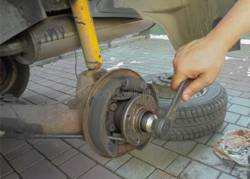 Reparation av en nav av av ett bakhjul en mans hand skruvar upp en låsmutter med en skiftnyckel arkivbild