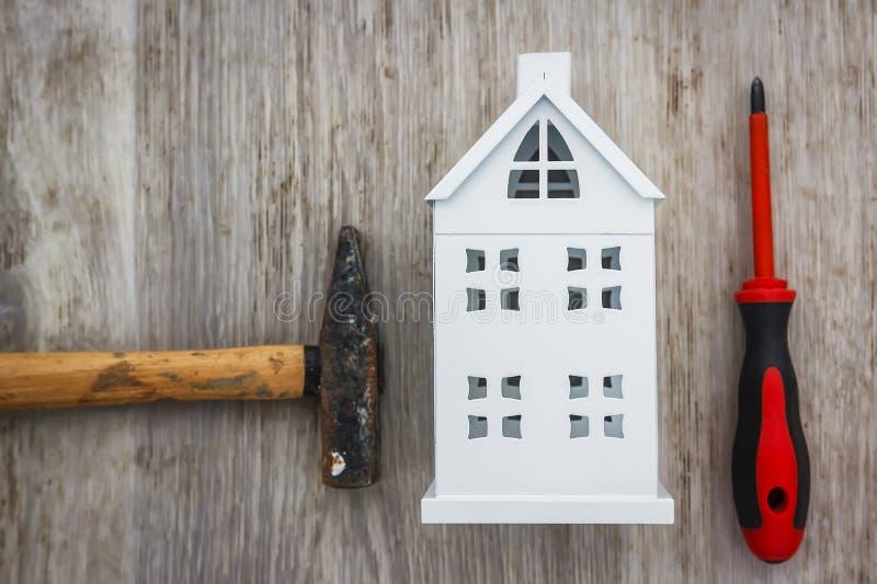 Reparation av husbegreppet hammare, skruvmejsel och miniatyrhus på träbakgrund Byggande hjälpmedelreparationshus arkivfoto