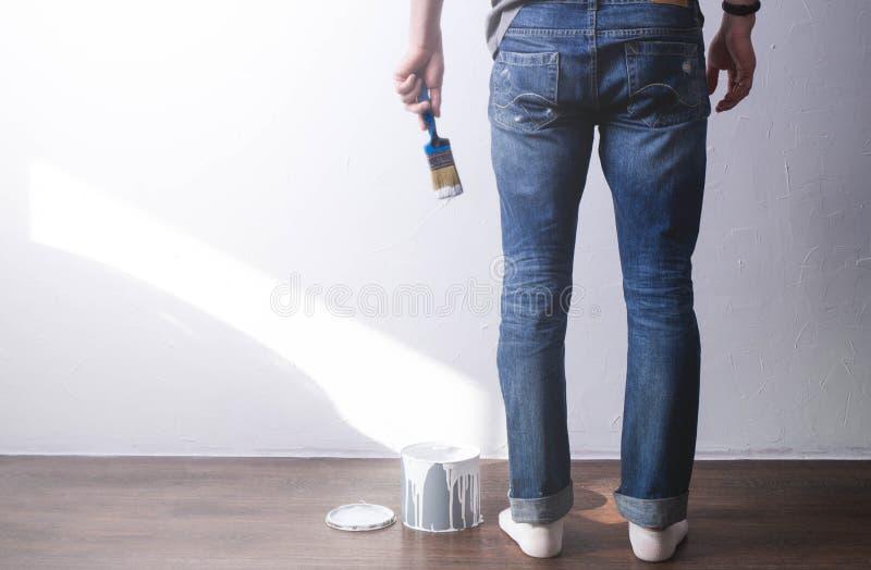 Reparation av huset: mannen ska måla väggen med en borste i vit Målarfärgen dryper från borsten arkivbilder