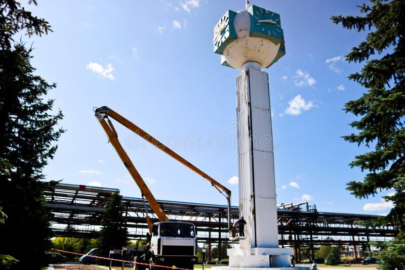 Reparation av tornklockan Arbetare på kranreparationsklocka-kolonnen, klockan på tornet, målarfärg, uppdatering, utför kosmetiska arkivfoto