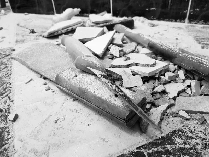 Reparation - byggnad med hjälpmedel bultar, släggan, köttyxan och en kniv med skärvor av tegelplattan royaltyfri bild