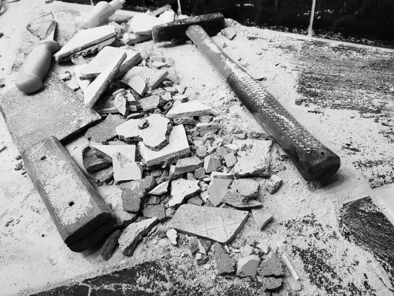 Reparation - byggnad med hjälpmedel bultar, släggan, köttyxan och en kniv med skärvor av tegelplattan royaltyfri foto
