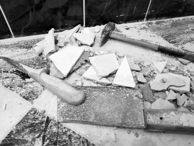 Reparation - byggnad med hjälpmedel bultar, släggan, köttyxan och en kniv med skärvor av tegelplattan arkivfoton