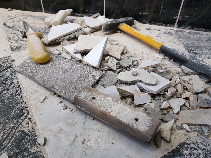 Reparation - byggnad med hjälpmedel bultar, släggan, köttyxan och en kniv med skärvor av tegelplattan arkivbilder