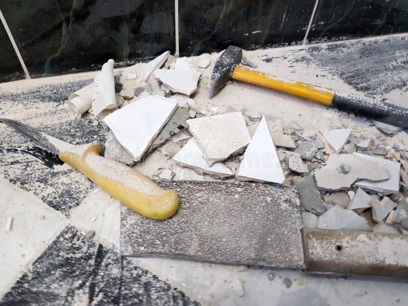 Reparation - byggnad med hjälpmedel bultar, släggan, köttyxan och en kniv med skärvor av tegelplattan fotografering för bildbyråer