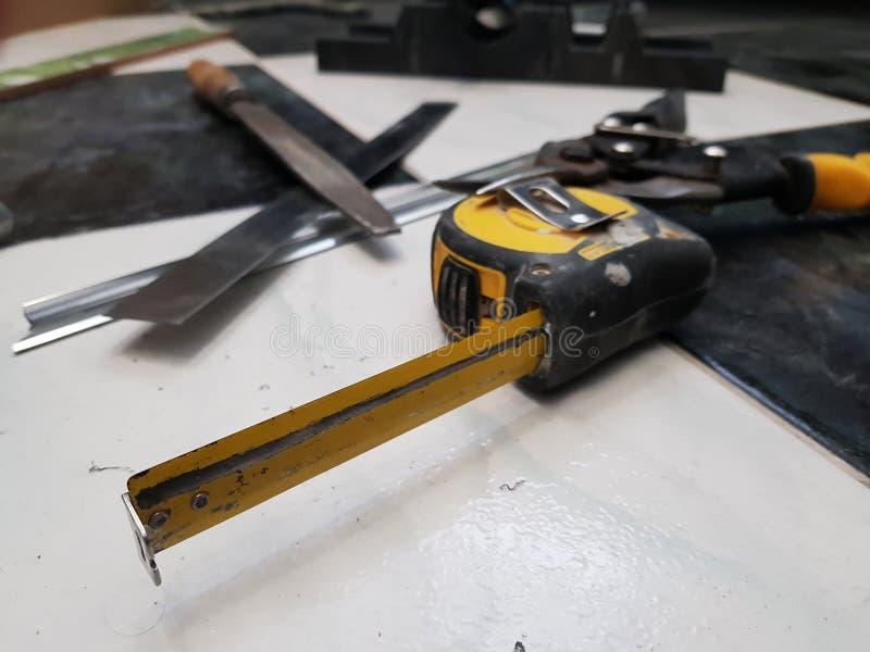 Reparation - byggnad med hjälpmedel, måttband, metallsax, mapp, metallkniv, blyertspenna, kniv, linjal arkivfoto
