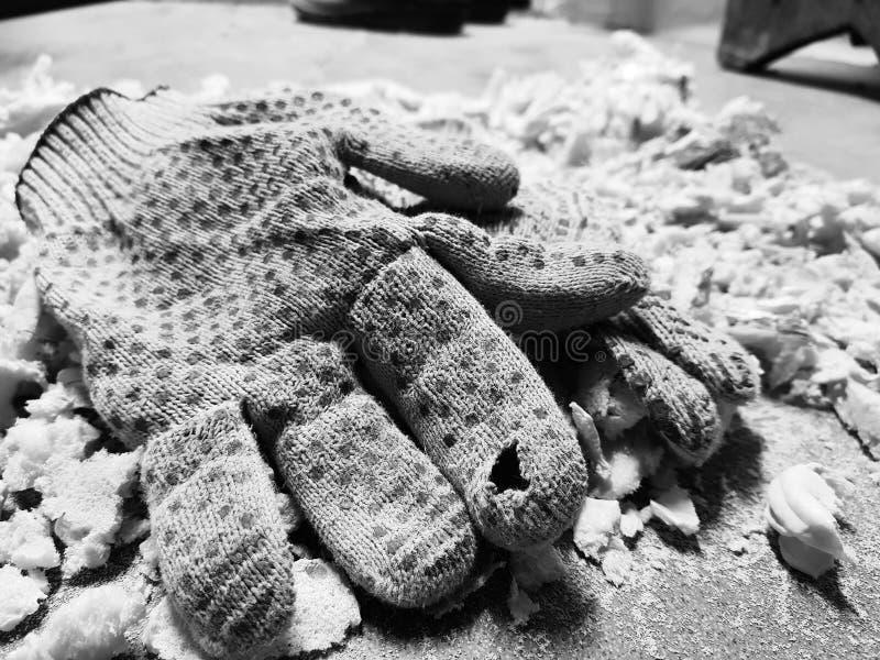 Reparation - klippa skum- och konstruktionshandskar på det belade med tegel golvet royaltyfria bilder