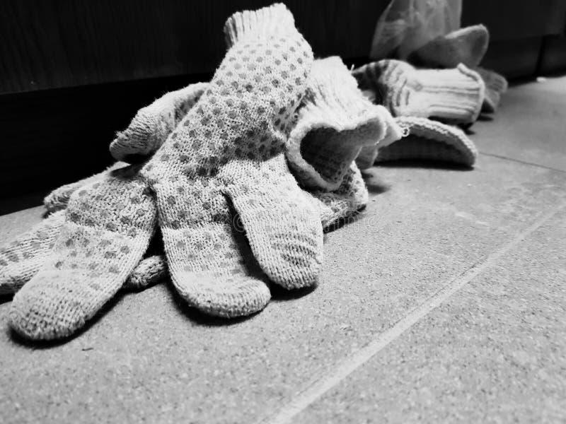 Reparation - klippa skum- och konstruktionshandskar på det belade med tegel golvet royaltyfri bild