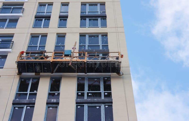 Reparation och återställande av en fasad av en hög byggnad royaltyfria bilder