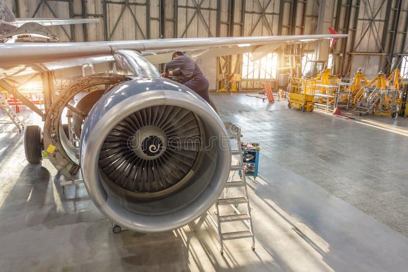 Reparationen för flygplanmotorn, mekaniker installerar omvända huvar arkivbild