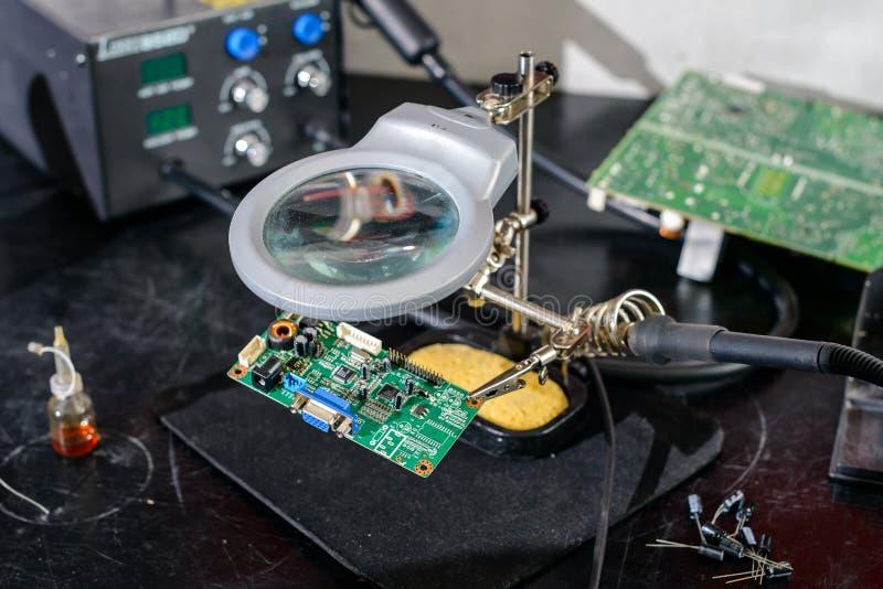 Reparationen shoppar av elektronisk utrustning och att löda stationen, förstoringsapparaten och den tredje handen arkivfoto
