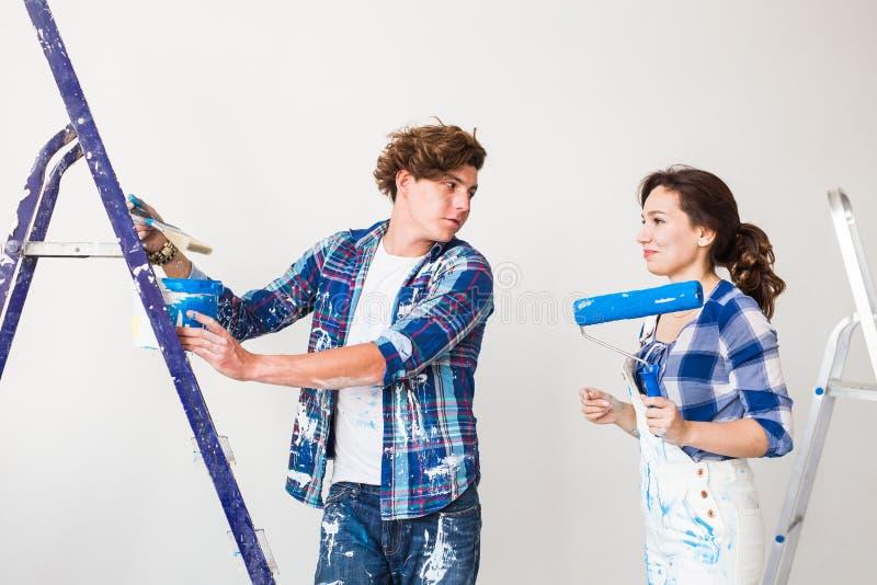 Reparations-, renovering- och förälskelseparbegrepp - ung familj som gör reparation och tillsammans målar väggar och att skratta arkivbild