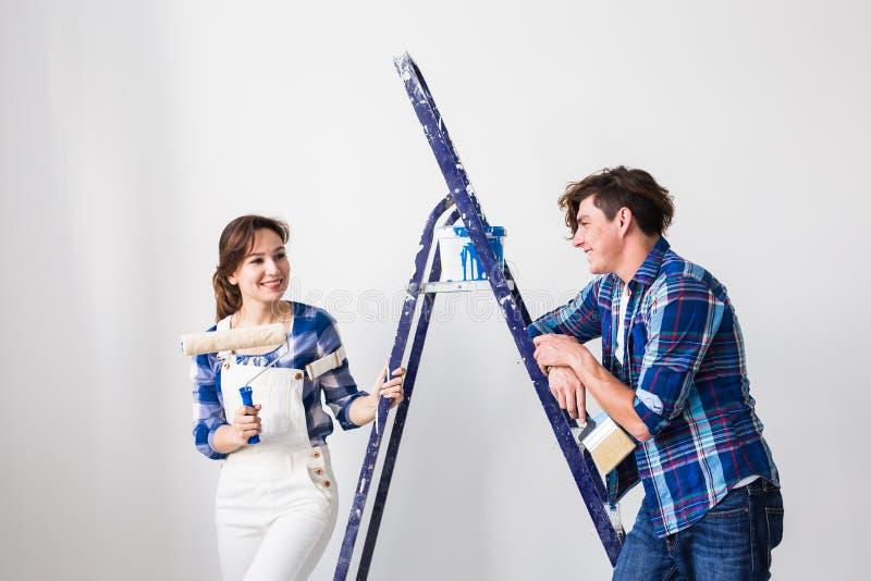 Reparations-, renovering- och förälskelseparbegrepp - ung kvinna och man som gör reparation med lyckliga framsidor arkivfoton