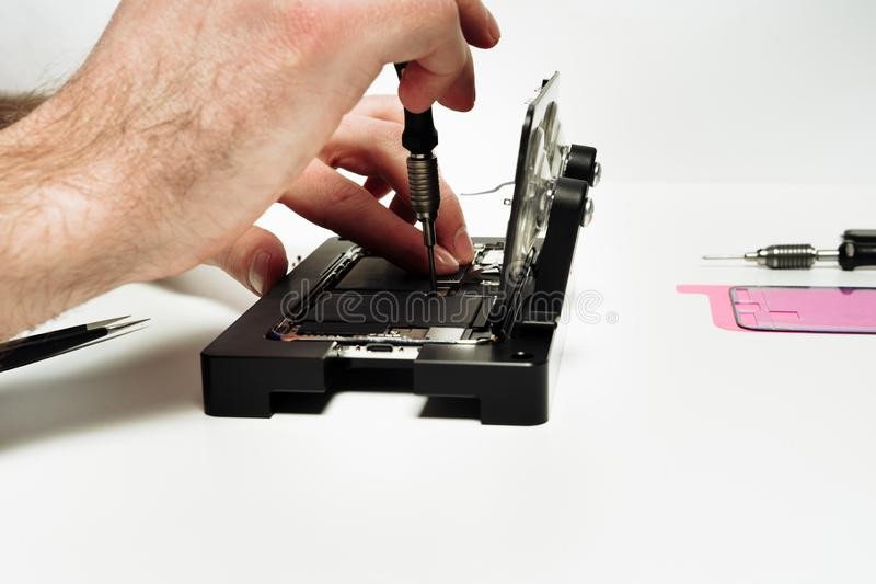 Reparationsarbetaren monterar den defekta brutna smartphonen arkivbild