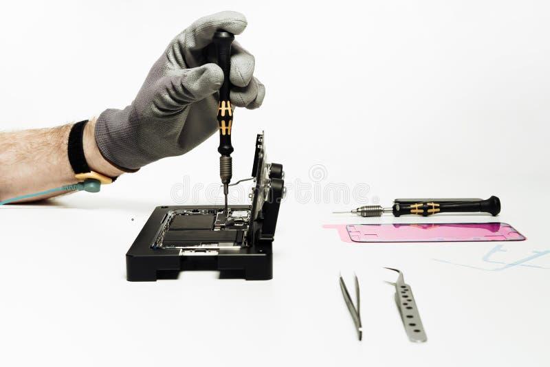 Reparationsarbetaren monterar den skadade brutna smartphonen arkivbilder