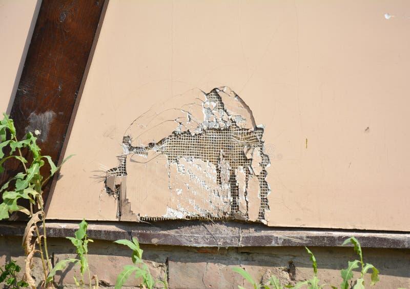 Reparationssprickor och hål i husväggstuckatur När du reparerar ett hål i en stuckaturvägg ska kräva lite patiens, och några övar royaltyfri bild