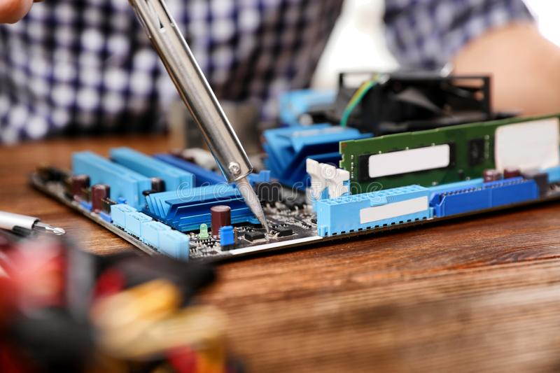 Reparatur des Motherboards mit L?tkolben auf Tabelle stockbilder