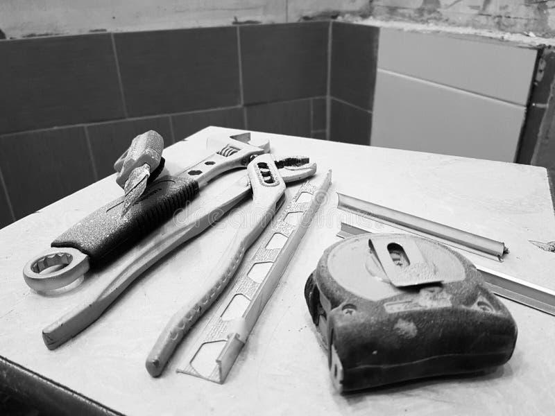 Reparatur - Gebäude mit Werkzeugen Schlüssel, Messer, Eisenmesser, justierbarer Schlüssel und Maßband auf einem Schemel lizenzfreies stockfoto