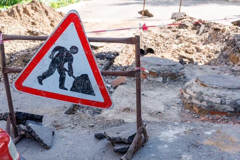 Reparatur von Straßenschildern im Hintergrund von Gruben stockfotos