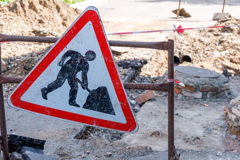 Reparatur von Straßenschildern im Hintergrund von Gruben stockfoto