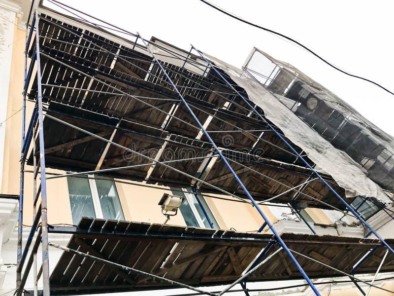 Reparaturarbeit über die Fassade des Gebäudes mithilfe des hölzernen Baugerüsts, Strukturen, Wiederherstellung des alten Hauses lizenzfreies stockfoto