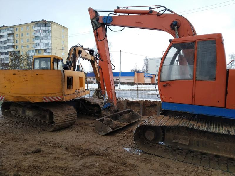Reparaturbauarbeiten, der Hydraulikbagger auf Gleiskettenfahrzeug zum Kurs der orange und gelben Farbe, Bodenbewegung in der Stad stockbild